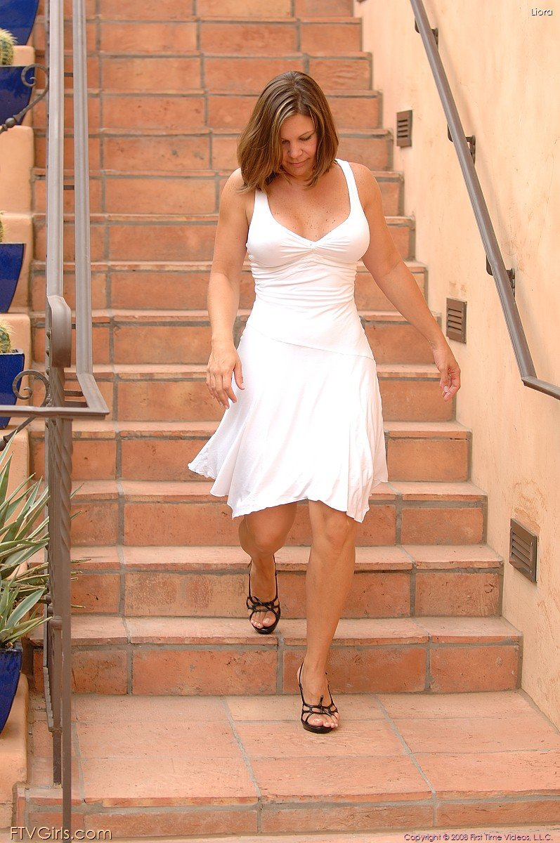 Mature beauty in a white dress showcasing her meaty white