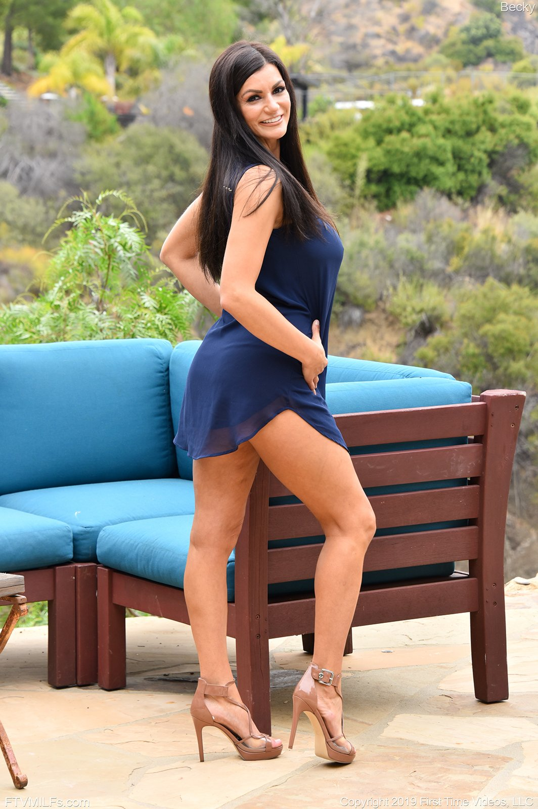 Dark-haired beauty in a blue dress bends over to show off